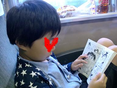 車内漫画を読む息子